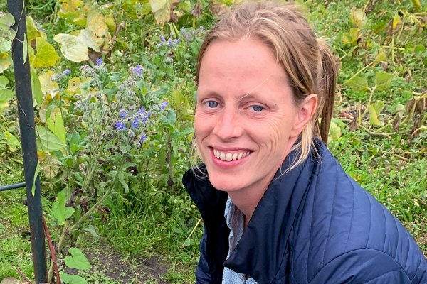 Eva Flendrie tussen de komkommerkruid op de Makkertuin